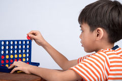 Little boy playing connect four game soft focus at eye contact indoor activities Royalty Free Stock Photo