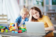 Little boy playing with construction blocks while his mother working on computer royalty free stock photos