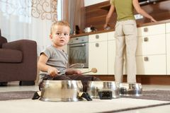 Little boy playing with cooking pots stock images
