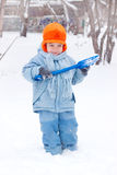 Little boy playing, digs snow Stock Images