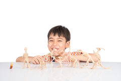 Little boy playing dinosaur fossil toy on the table indoor activities Stock Image