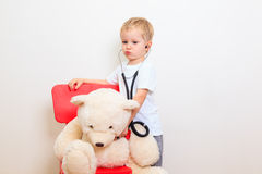Little boy playing doctor Stock Images
