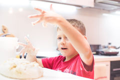 Little boy playing with dough in the kitchen Royalty Free Stock Photos