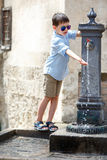 Little boy playing with drinking water fountain in Italy Stock Photos