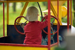 A little boy is playing and driving a toy train Royalty Free Stock Images