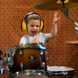 Little boy playing drums with protection headphones stock photo