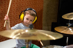 Little boy playing drums with protection headphones stock photography