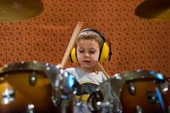 Little boy playing drums with protection headphones Royalty Free Stock Image