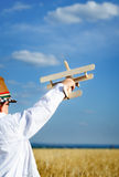 Little boy playing in farmland with a toy airplane Royalty Free Stock Photo