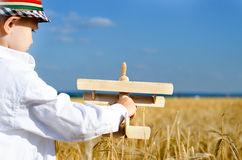 Little boy playing in farmland with a toy airplane Royalty Free Stock Photos