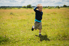 Little boy playing in a field near the big stones Royalty Free Stock Photography