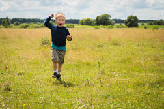 Little boy playing in a field near the big stones Stock Images