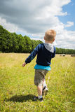 Little boy playing in a field near the big stones Stock Image