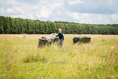 Little boy playing in a field near the big stones Royalty Free Stock Photo