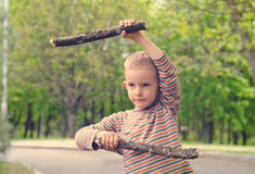 Little boy playing with fighting sticks Stock Photo