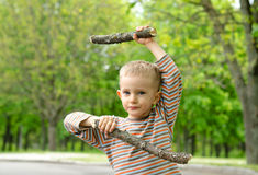 Little boy playing with fighting sticks Royalty Free Stock Image