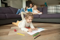Kids drawing reading book with parents, family activities at hom. Little boy playing on floor drawing with colored pencils while parents and girl daughter Royalty Free Stock Photo