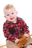Little boy playing on the floor with maple leaves. Stock Image