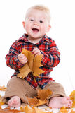 Little boy playing on the floor with maple leaves. Royalty Free Stock Images