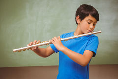 Little boy playing flute in classroom Royalty Free Stock Photos