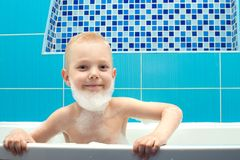 A little boy is playing with foam in the bathroom. A little boy is playing royalty free stock image