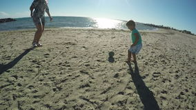 Little boy playing football on the beach stock video footage