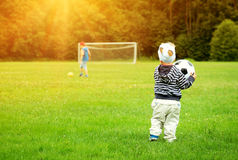Little boy playing football on the field with gates Royalty Free Stock Image