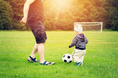 Little boy playing football on the field with gates Stock Images