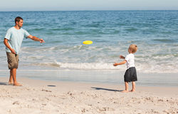 Little boy playing frisbee with his father Stock Images