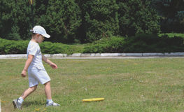 Little boy playing Frisbee in the park. The boy 6-7 years dressed total white. small player in motion Stock Images