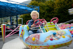 A little boy playing in a fun fair carousel Royalty Free Stock Images