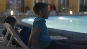 Little boy playing game on smartphone near pool. Little boy playing game on smartphone. Children are entertained in the pool area online. Kids have digital fun stock video