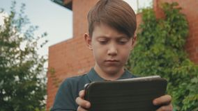 Little boy playing games on his touchscreen tablet outdoors in front of the house covered in greenery stock video footage