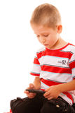 Little boy playing games on smartphone. Leisure, technology and internet concept - little boy with smartphone playing games or reading text message Stock Photography