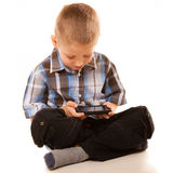 Little boy playing games on smartphone Royalty Free Stock Images