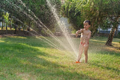Little boy playing with the garden sprinkler. In summer time royalty free stock photo