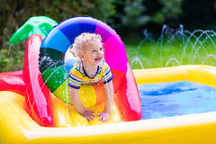 Little boy playing in garden swimming pool Stock Images