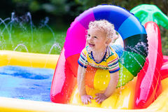 Little boy playing in garden swimming pool Royalty Free Stock Photos