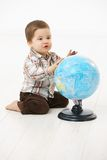 Little boy playing with globe. Cute little kid (2-3 years) sitting on floor playing with globe over white background Stock Image