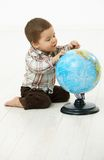 Little boy playing with globe. Cute little kid (2-3 years) sitting on floor playing with globe over white background Stock Photography