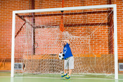 Little boy playing in the goals at soccer. Little boy playing in the goals at a game of soccer on an indoor court practicing his skills as he prepares to throw Royalty Free Stock Photos