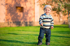 Little boy playing on green grass Stock Photos