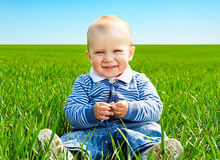 Little boy playing in the green grass Stock Photos