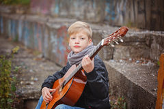 Little boy playing guitar in autumn cold day.  Children's intere Stock Images