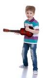 Little boy playing guitar Stock Photos