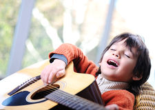 Little boy playing guitar Stock Photography