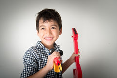 Little boy playing guitar and sing with microphone Stock Photo