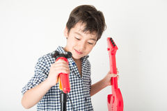Little boy playing guitar and sing with microphone Royalty Free Stock Images