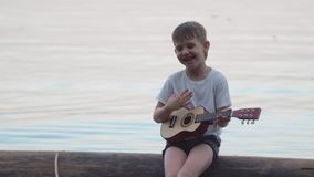 Little boy playing guitar sitting on a log in the sea. He smiles and sings merry songs stock video