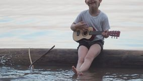 Little boy playing guitar sitting on a log in the sea. He smiles and sings merry songs stock video footage
